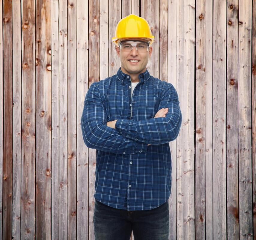 A picture of a worker standing in front of a fence with arm crossed and hard hat on