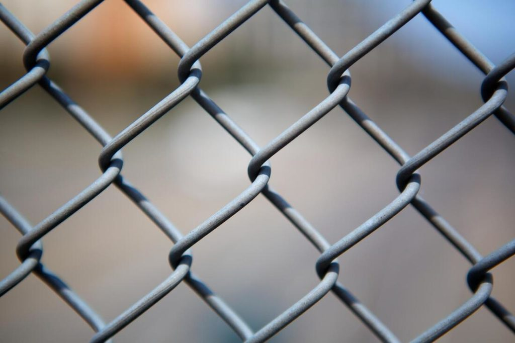 A close up picture of a chain link fence with a blurred backround