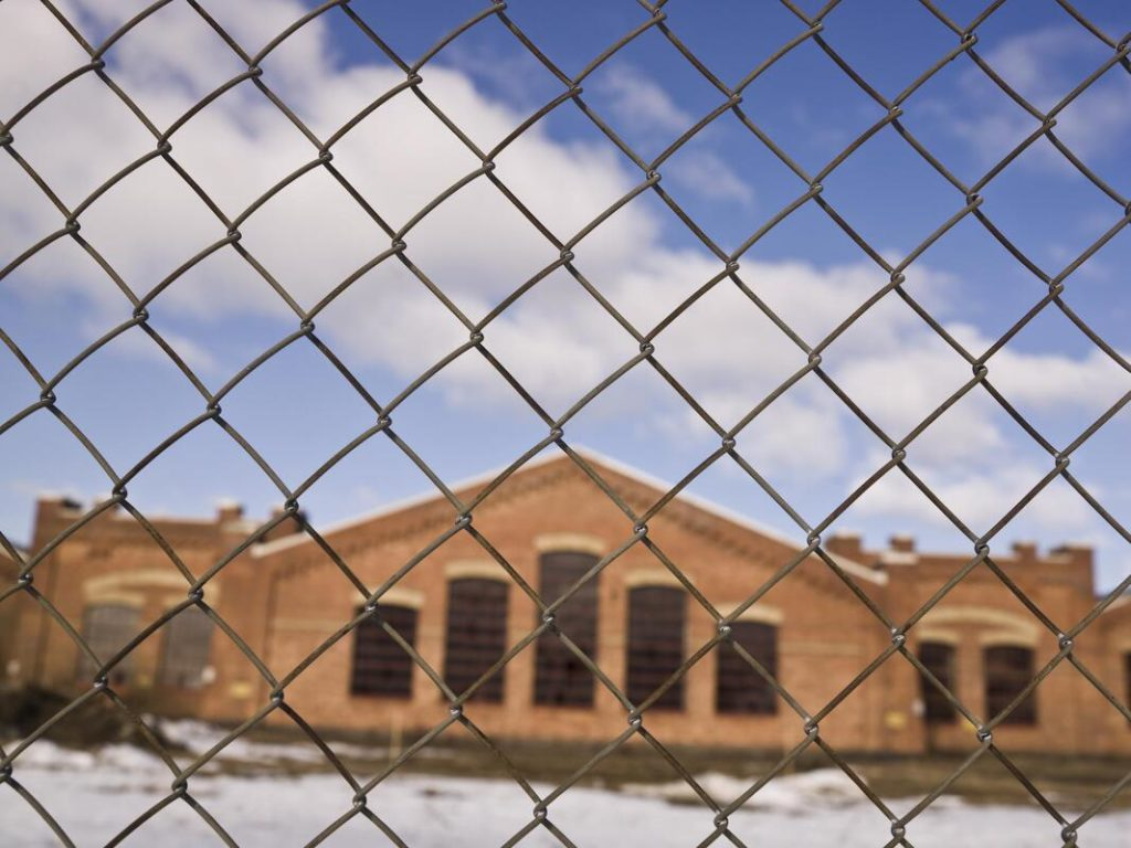 A picture of a chain link fence with a building in the back round looking through the fence