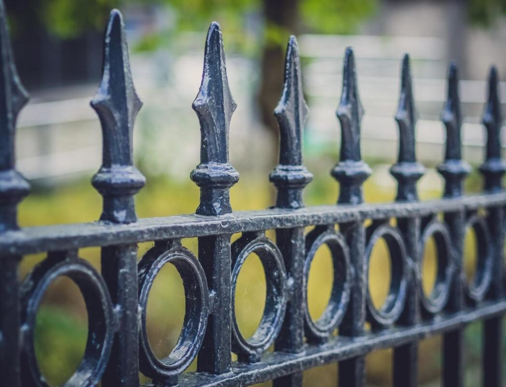 Picture of a black fence close up and everything is blurred in the backround