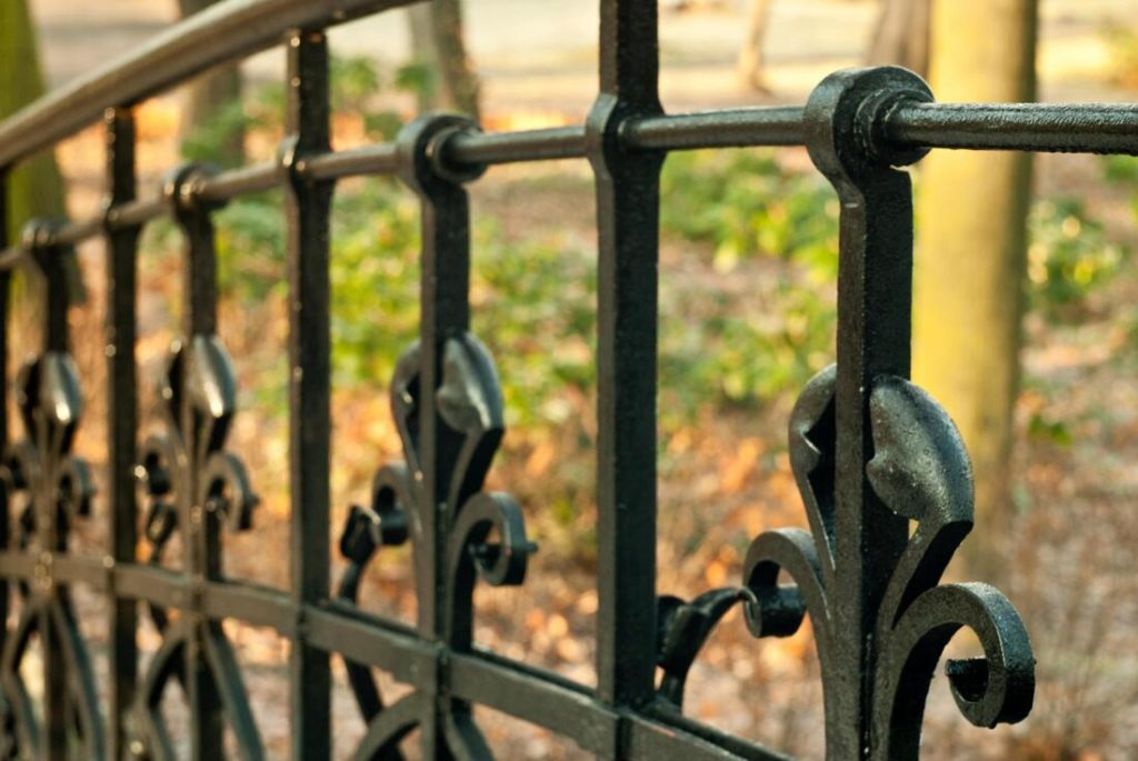 Close up picture of a black iron fence