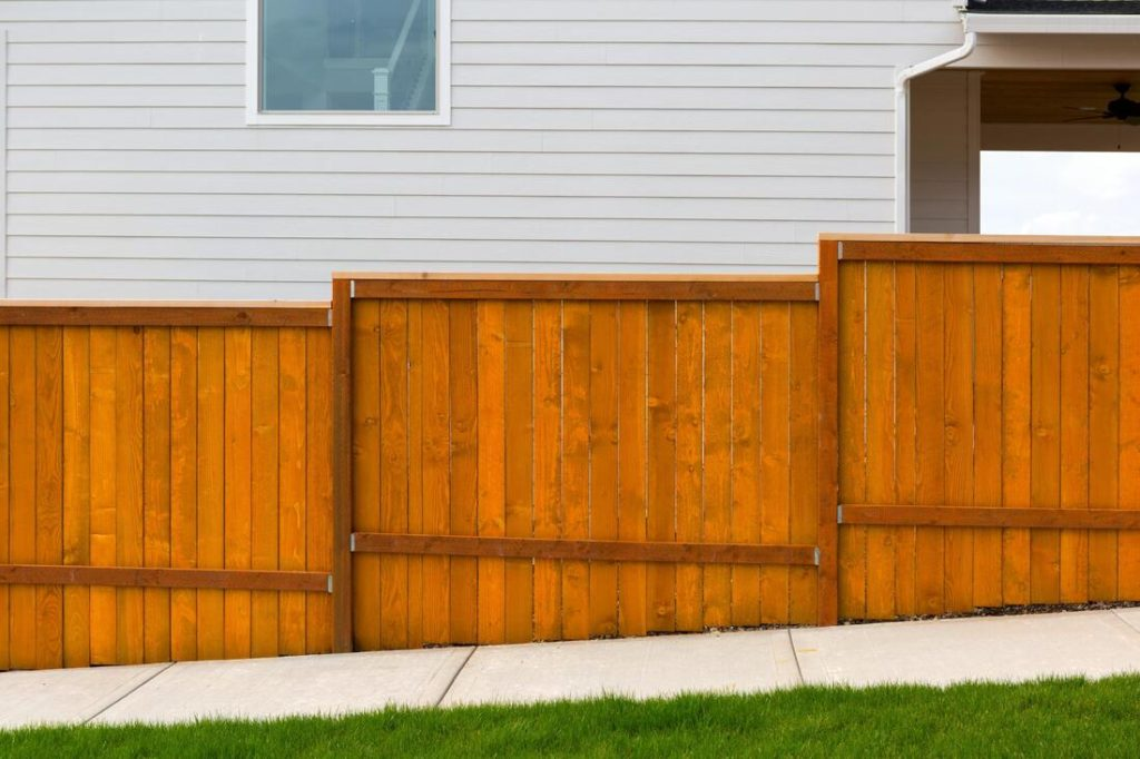 A picture of a fence going up hill next to a house and sidewalk