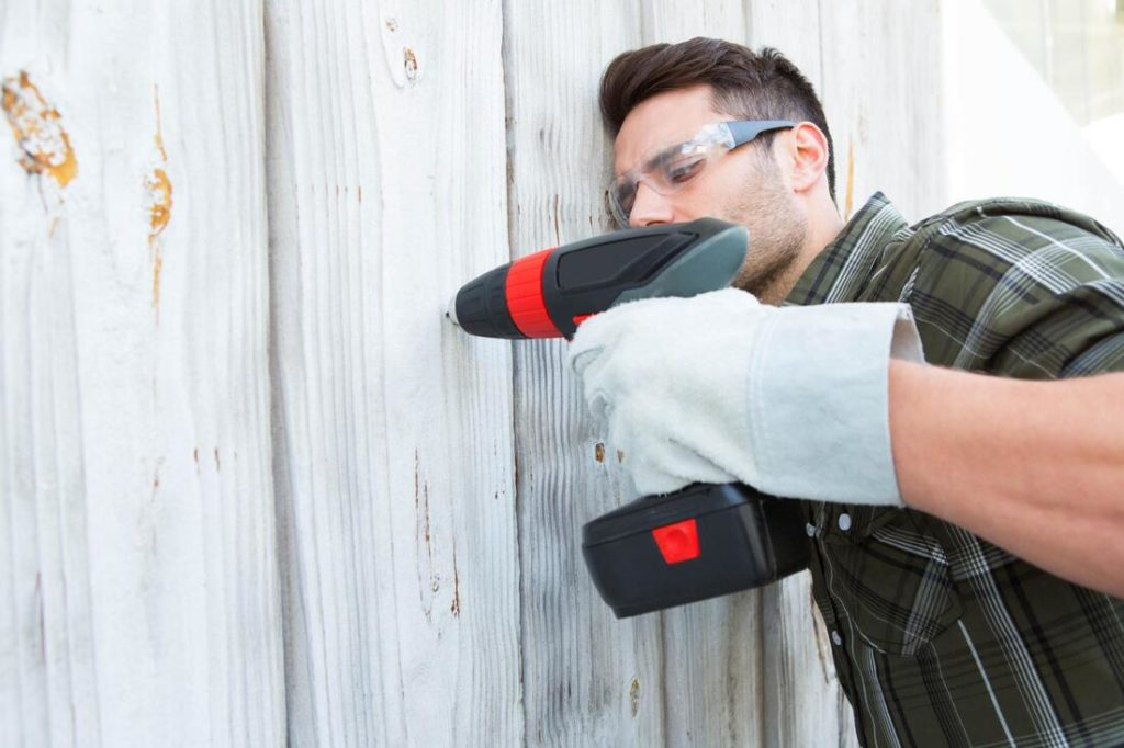 A picture of a guy drilling fence pieces together for a fence repair