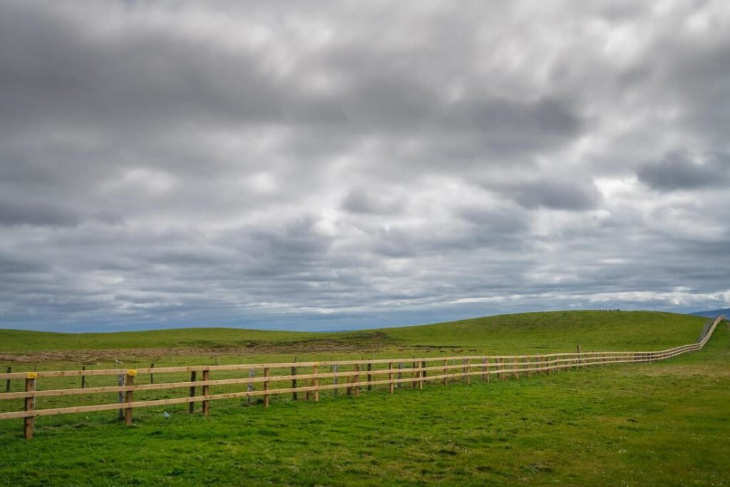 A picture of a split rail fence with a cloudy sky and green grass